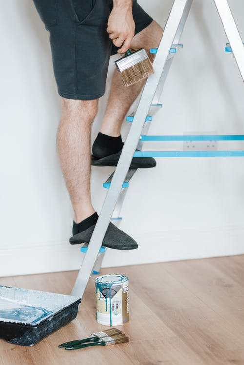 Side view of creative male in casual clothes painting wall with brush on steps while renovating room in soft daylight