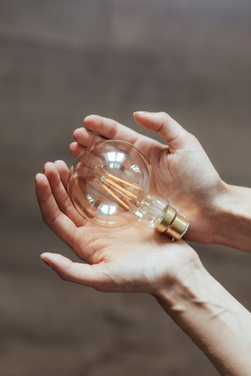 Unrecognizable woman demonstrating light bulb in hands - Being Energy Efficient At Home