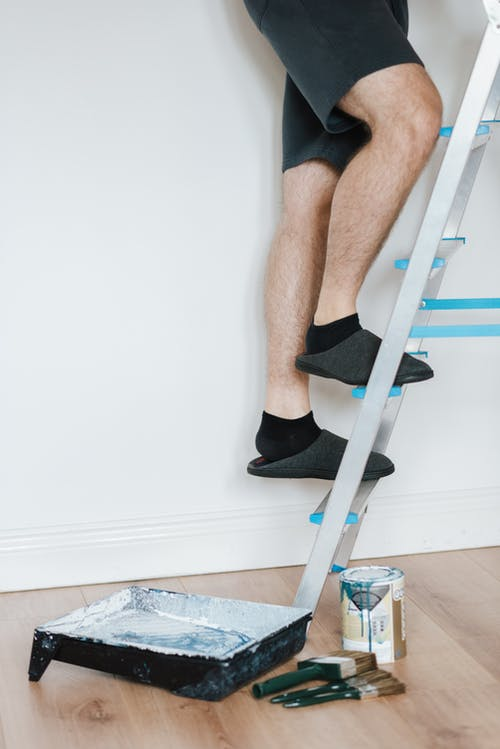 Painter climbing on stepladder near brushes