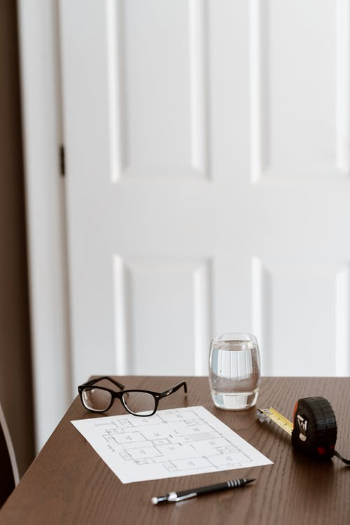 From above of wooden desk with scheme and pen with glasses and tape measure near glass of water in light room