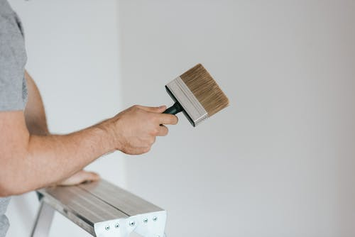 Side view of crop faceless painter in casual clothes holding paintbrush while leaning on stepladder on gray background in soft daylight