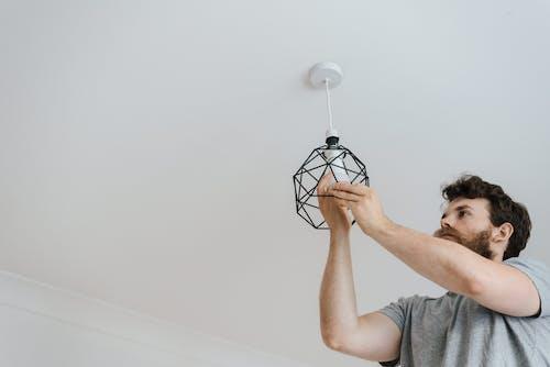 Man screwing light bulb into lamp
