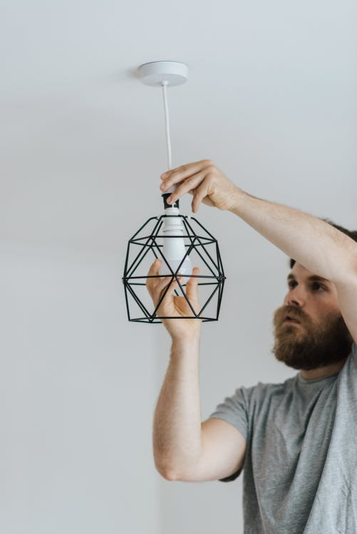 Concentrated repairman screwing light bulb in stylish lamp hanging on ceiling of new flat