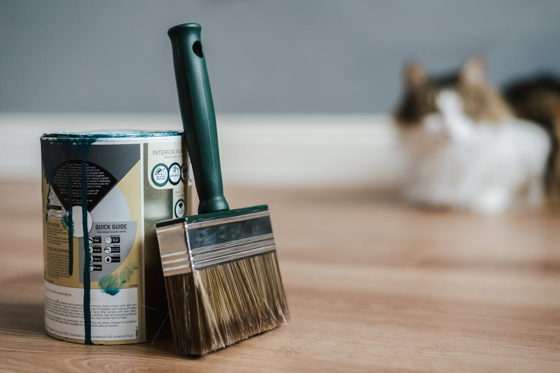 Paint brush near can on floor at home