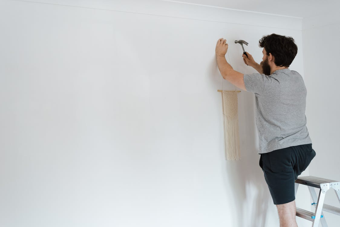 Anonymous hipster man putting decor on wall in new house