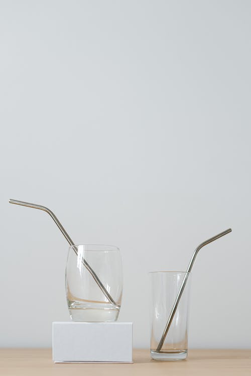 Various glasses with shiny transparent surface and drinking tubes on cardboard box on desk