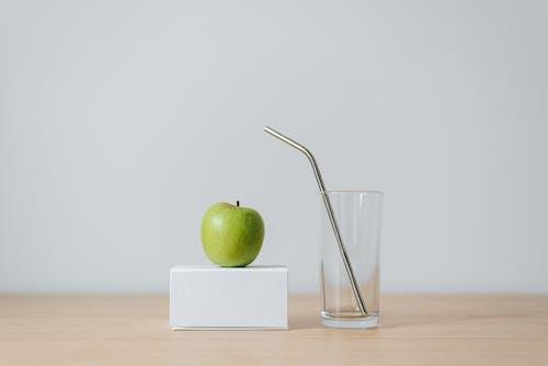ストローと空のガラスの近くのボックスに青リンゴ