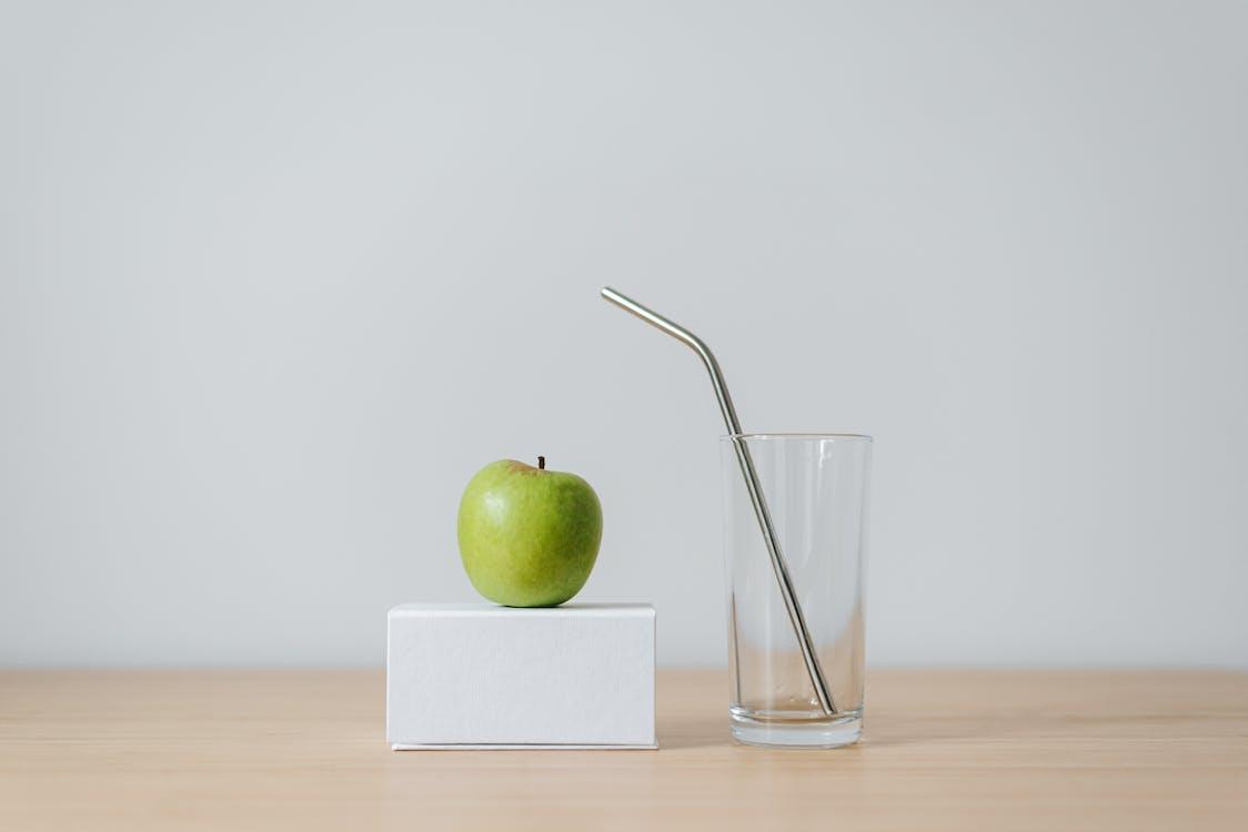 Green apple on box near empty glass with straw
