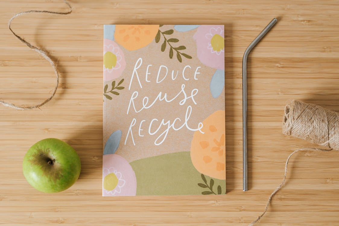 Top view of book with Reduce Reuse Recycle inscriptions near green apple and bobbin of thread on table