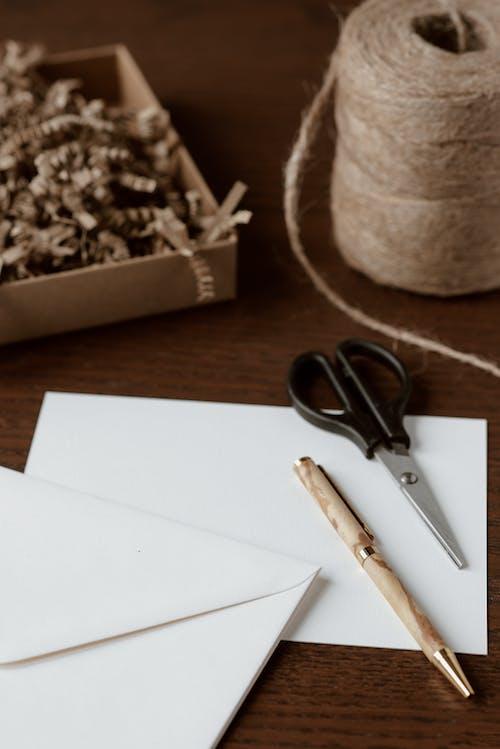 Handmade envelope near pen and scissors on table