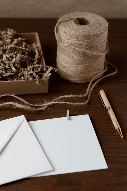 From above of empty handmade envelope near pen and bobbin of thread on table with box full of dry shavings
