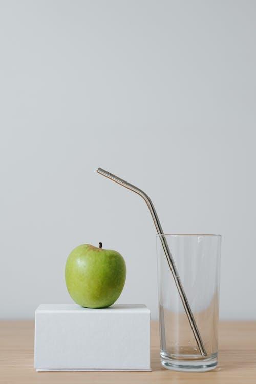 Tasty apple on cardboard box near glass with straw