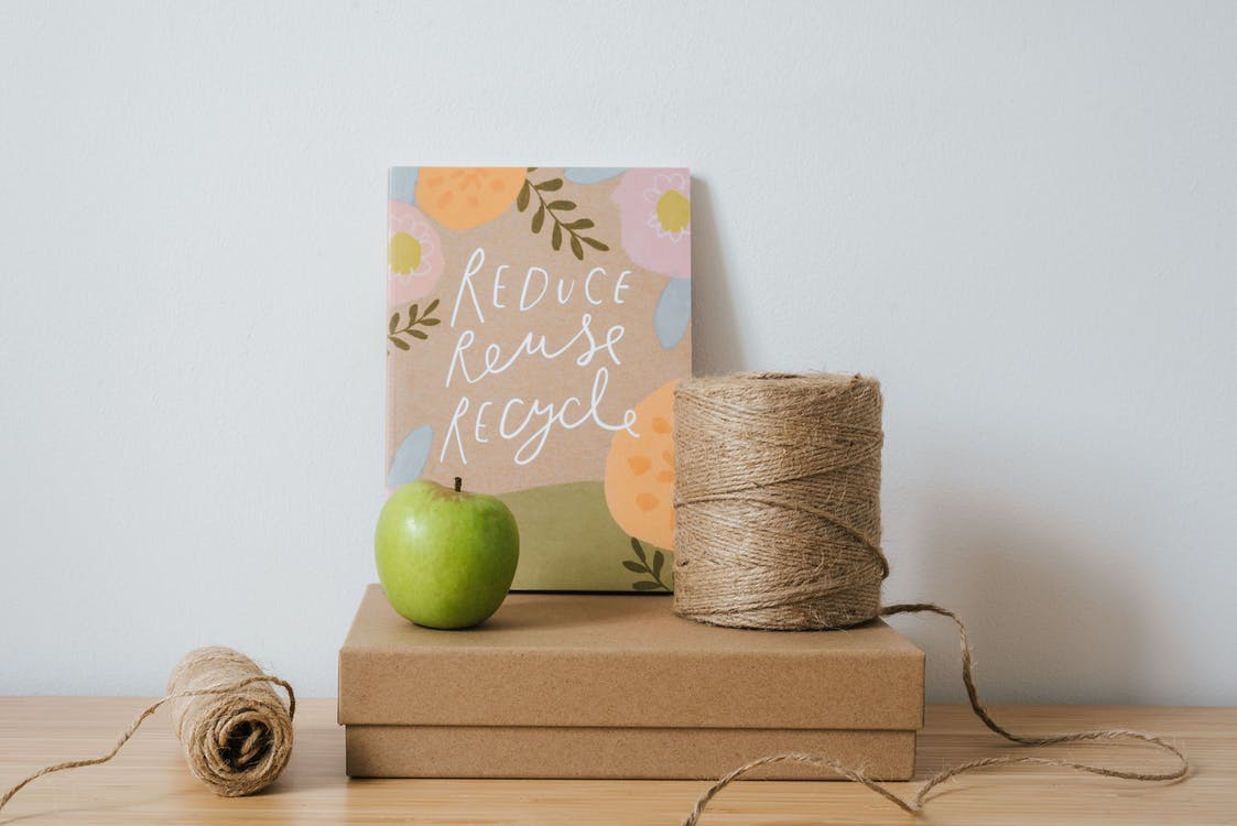 Book with illustration on cover and titles on carton box near bobbins of threads on white background