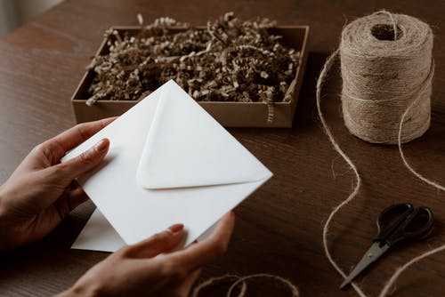 From above of crop anonymous craftswoman with blank envelope near spool of organic thread and box with shavings at desk