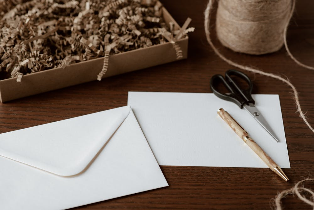 Envelope and pen placed on a table. | Photo: Pexels