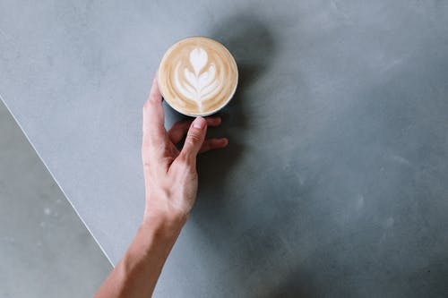 Person Holding Cappuccino on White Ceramic Cup
