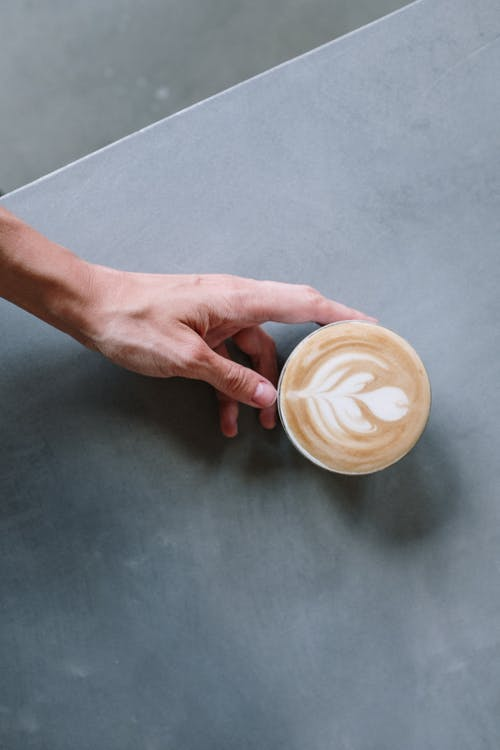 Person Holding White and Brown Ceramic Mug
