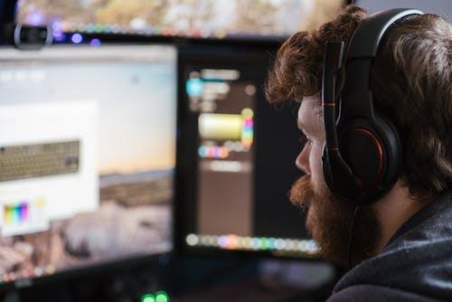 Crop man in headphones working on computer