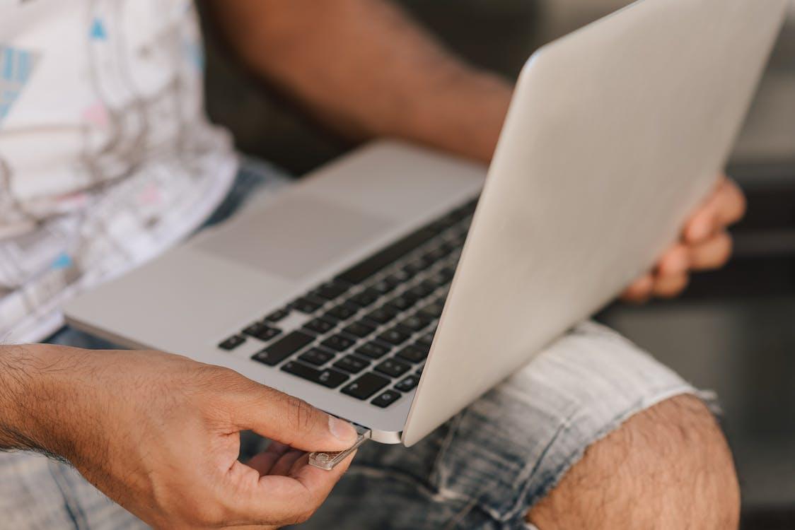 Crop faceless man using laptop and inserting flashcard
