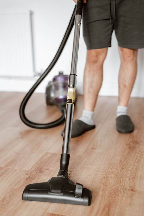 Crop anonymous male doing housework and vacuuming parquet floor in apartment in daylight
