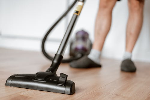 Man cleaning floor with vacuum cleaner