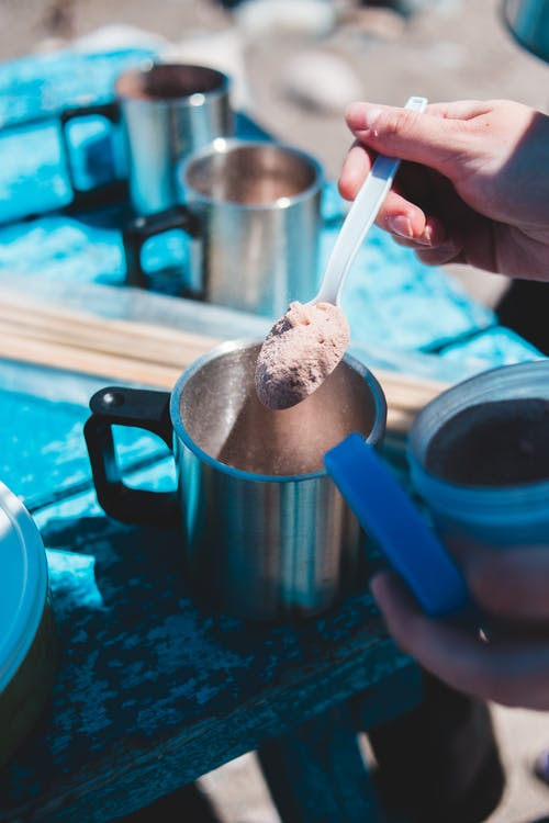 Crop traveler with instant coffee powder and metal mug outdoors