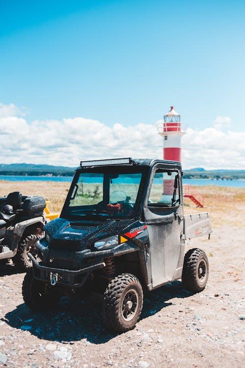 Old ATV on sandy sea shore behind lighthouse