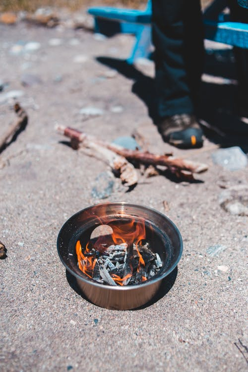 Crop traveler near bowl with fire and ash