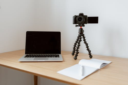 Modern workplace consisting of netbook camera on tripod near opened planner with pen on wooden table