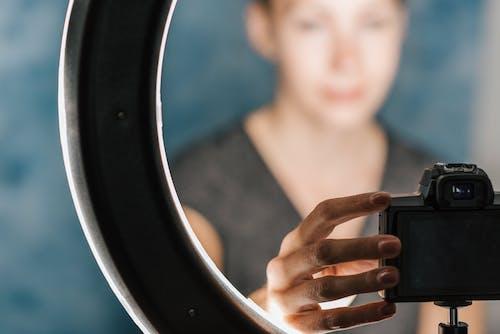 Женщина проверяет фотоаппарат возле студийной лампы