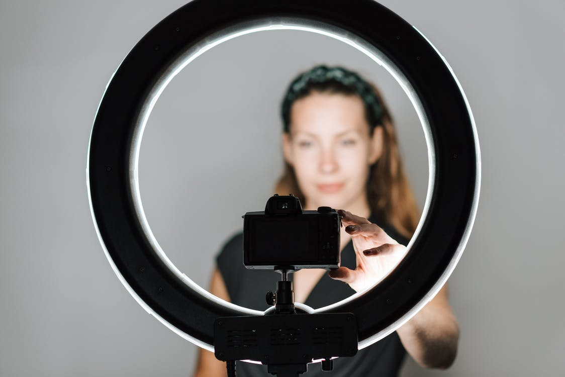 Young female taking self portrait with modern photo camera and studio lamp on white background