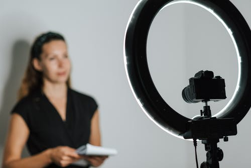 Young woman recording vlog with photo camera