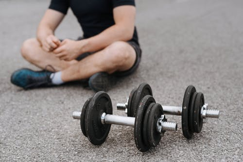 Man with dumbbells in lotus pose on asphalt road