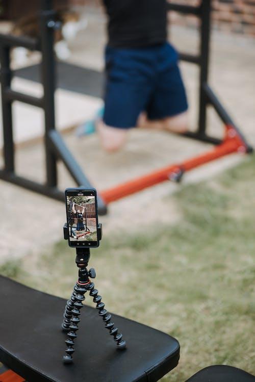 Man recording video of training on horizontal bar