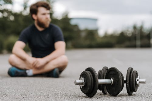 Young male with beard resting after workout on asphalt road with heavy dumbbells on gloomy day in selective focus