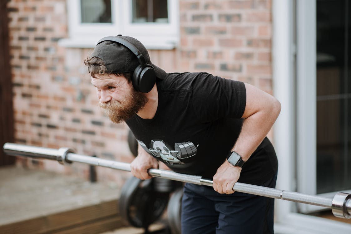 Brutal male with headphones pulling massive metal barbell on blurred background of brick house