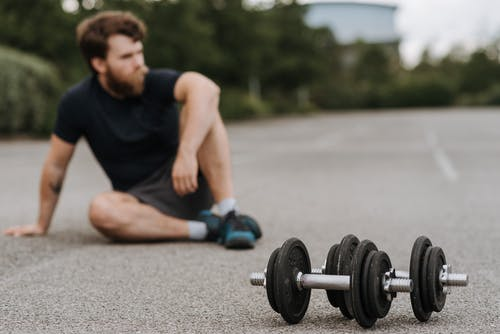 Pensive sporty man sitting on asphalt road with dumbbells