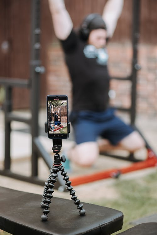 Sporty trainer recording video of workout on horizontal bar with smartphone in soft focus