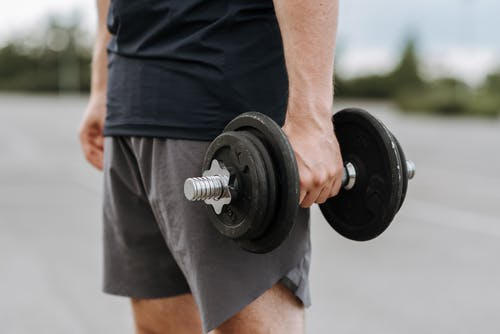 Crop anonymous male in activewear lifting heavy iron dumbbell on blurred background of street