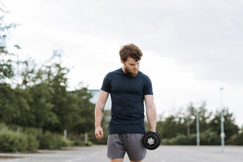 Serious sportsman looking down doing exercise with dumbbell while training on sports ground