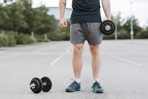 Crop unrecognizable male with great stamina lifting heavy dumbbells while doing exercises alone on paved ground