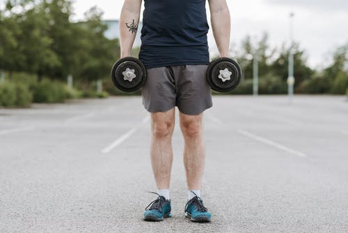 Man with strong hands lifting dumbbells