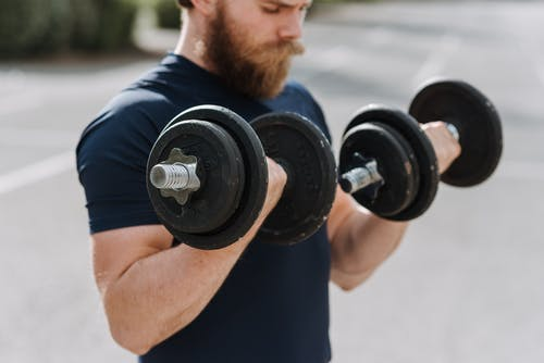 Crop sporty male making effort doing exercise with dumbbells while working out on blurred background of sports ground