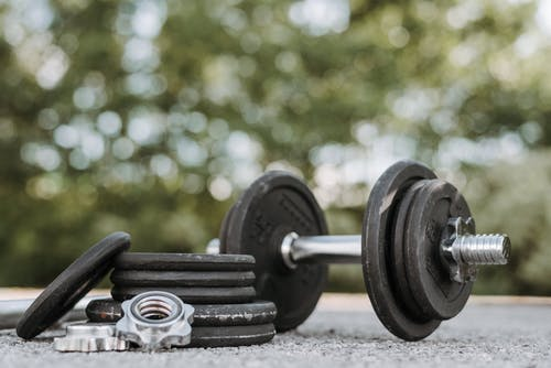 Ground level of adjustable dumbbell on stainless steel bar near plates and screw collars on rough walkway on street