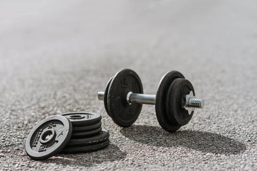 Dumbbell near pile of plates on pavement in sunlight
