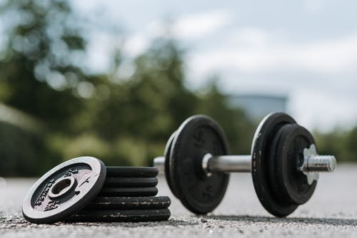 Dumbbell with heap of plates on asphalt road