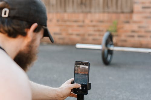 Crop anonymous unshaven sportsman in cap taking photo of barbell on cellphone on pavement in town
