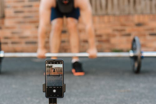 Unrecognizable bodybuilder lifting barbell behind smartphone recording video in town