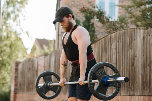 Hipster sportsman lifting barbell while working out on street