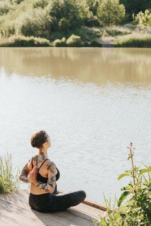 Anonymous tattooed woman showing Reverse Prayer pose near river
